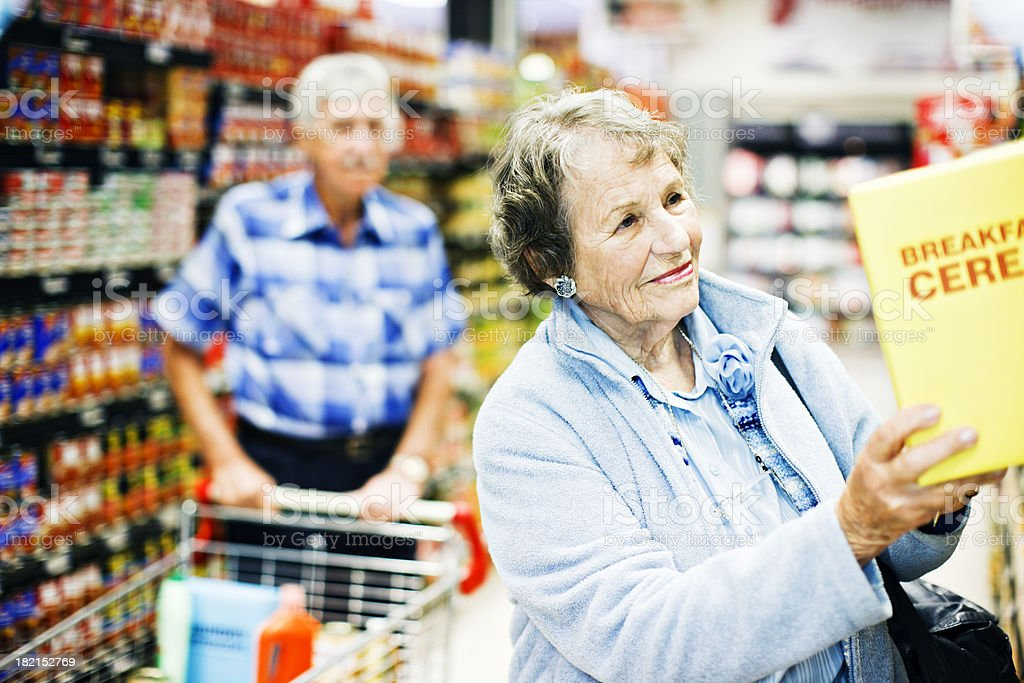 Happy senior woman finds favorite cereal in supermarket stock photo