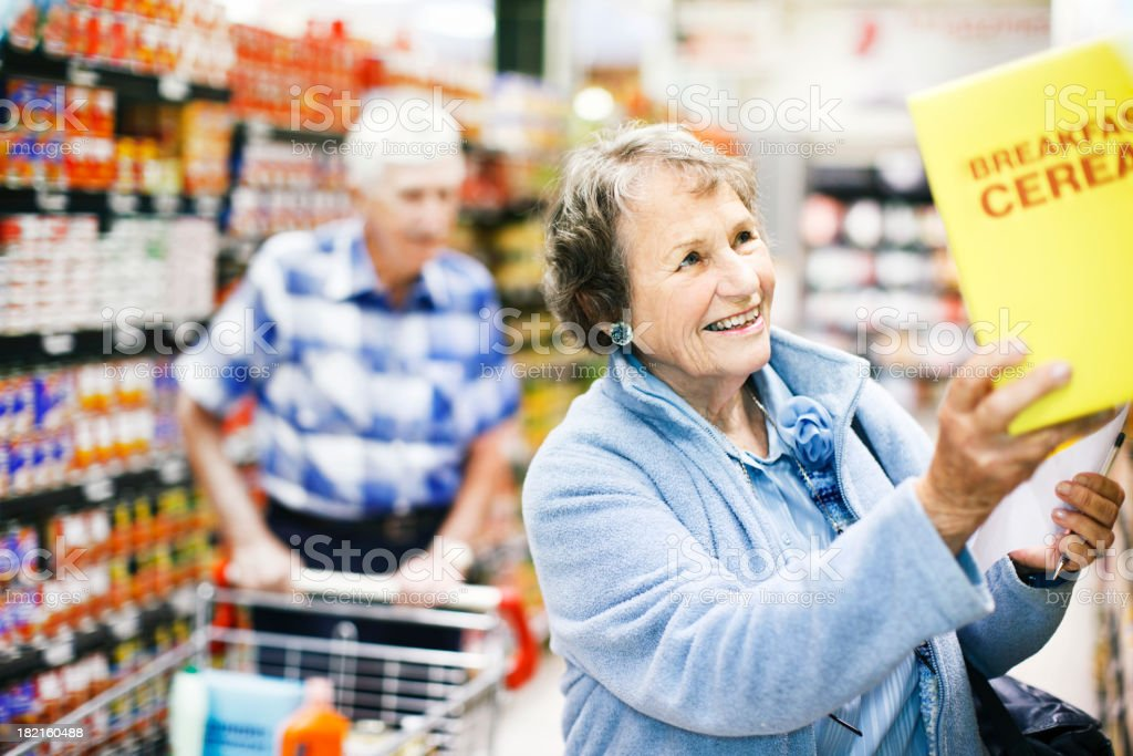 Happy senior woman finds favourite cereal in supermarket stock photo