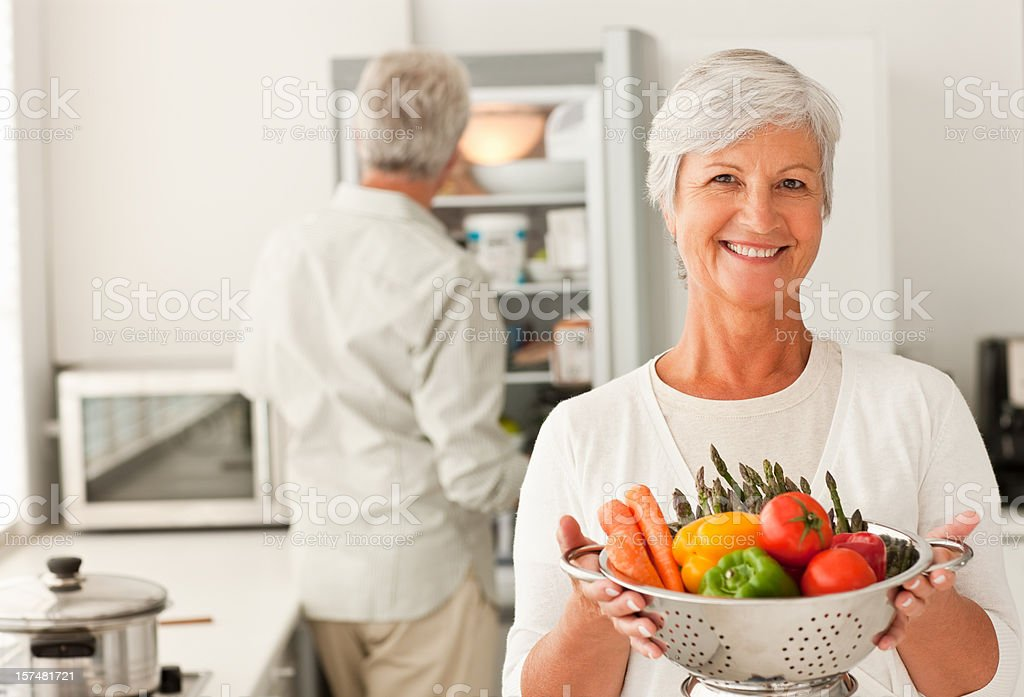 Happy senior woman holding a bowl full of vegetables royalty-free stock photo