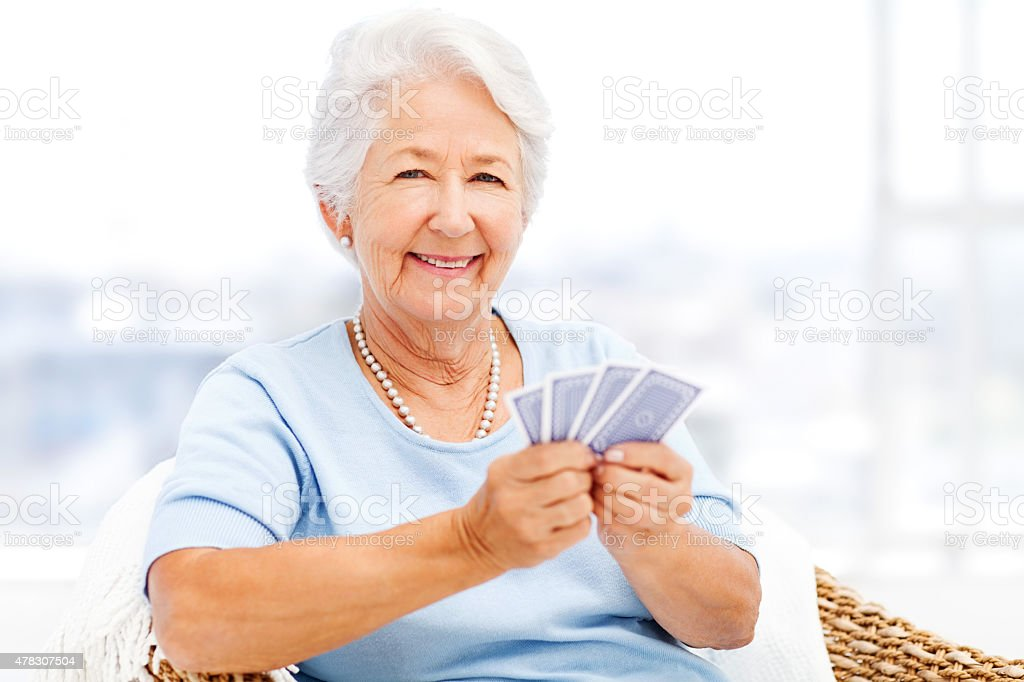 Happy Senior Woman Holding Cards While Sitting On Chair stock photo