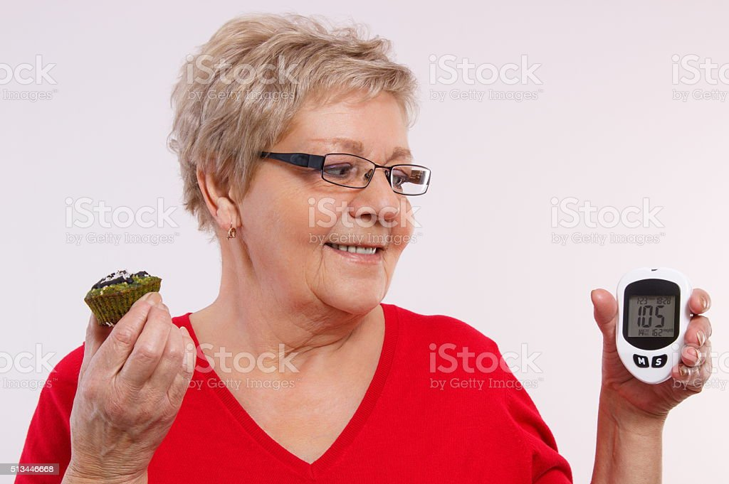 Happy senior woman holding glucometer and fresh cupcake stock photo