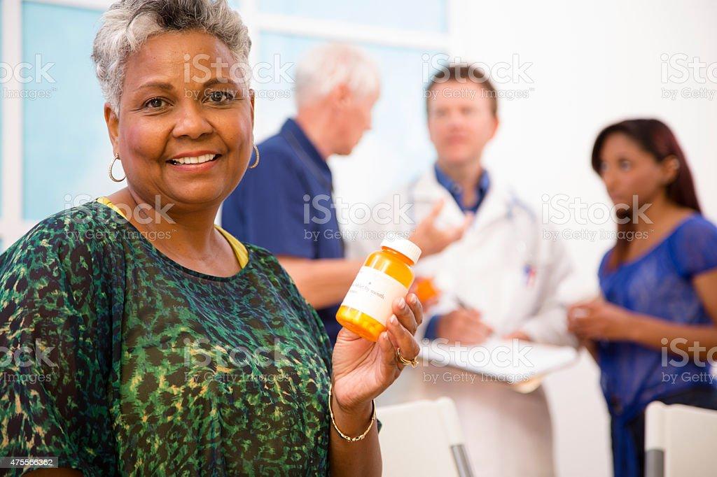 Happy senior woman holds prescription medication. Doctor, patients background. stock photo