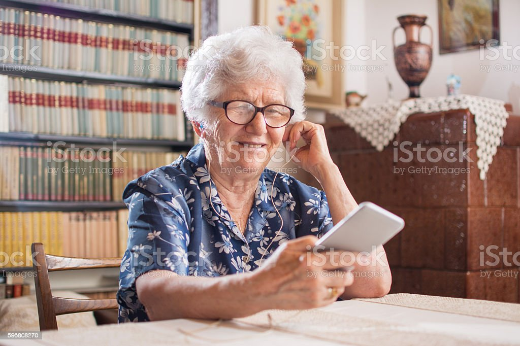 Happy senior woman listening to music on smartphone at home. stock photo