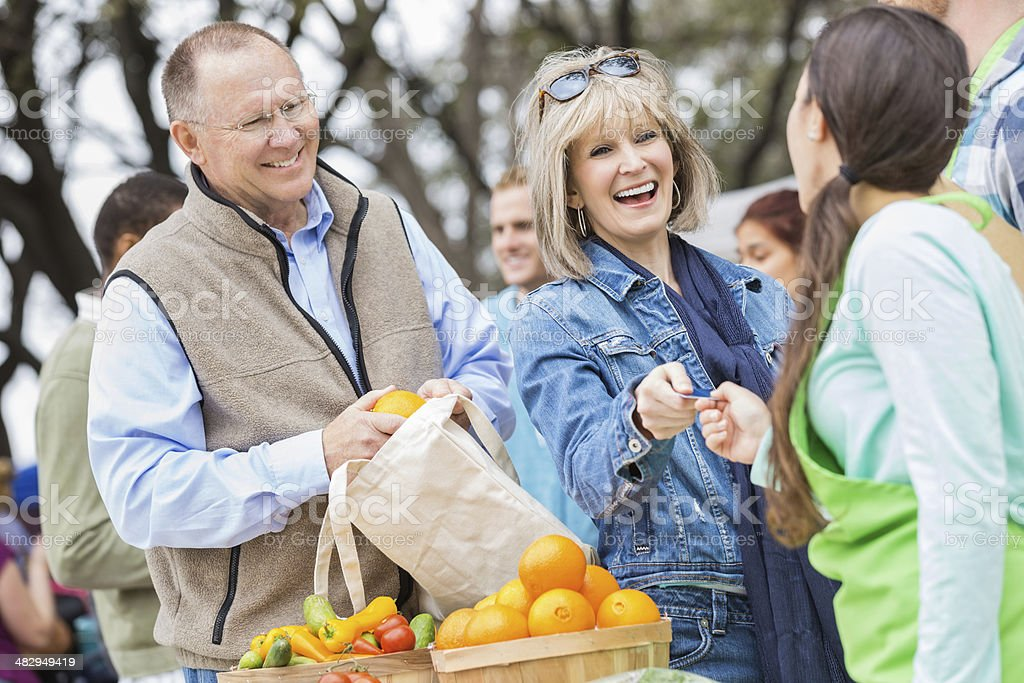 Happy senior woman paying for produce at local farmers market stock photo