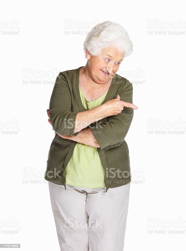 Happy senior woman pointing down isolated against white stock photo