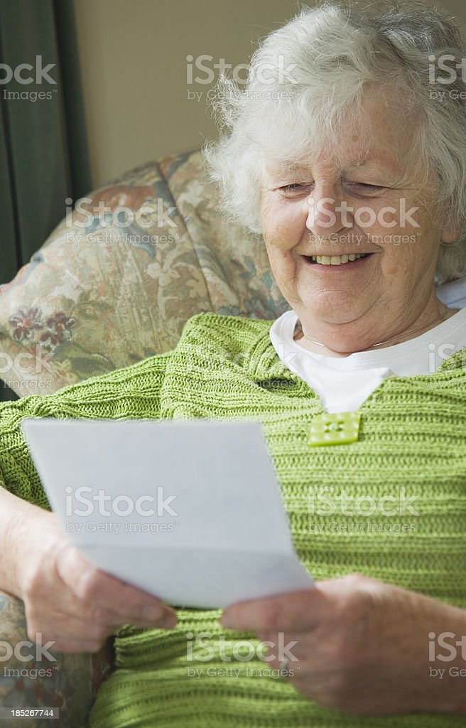 Happy senior woman reading a letter royalty-free stock photo