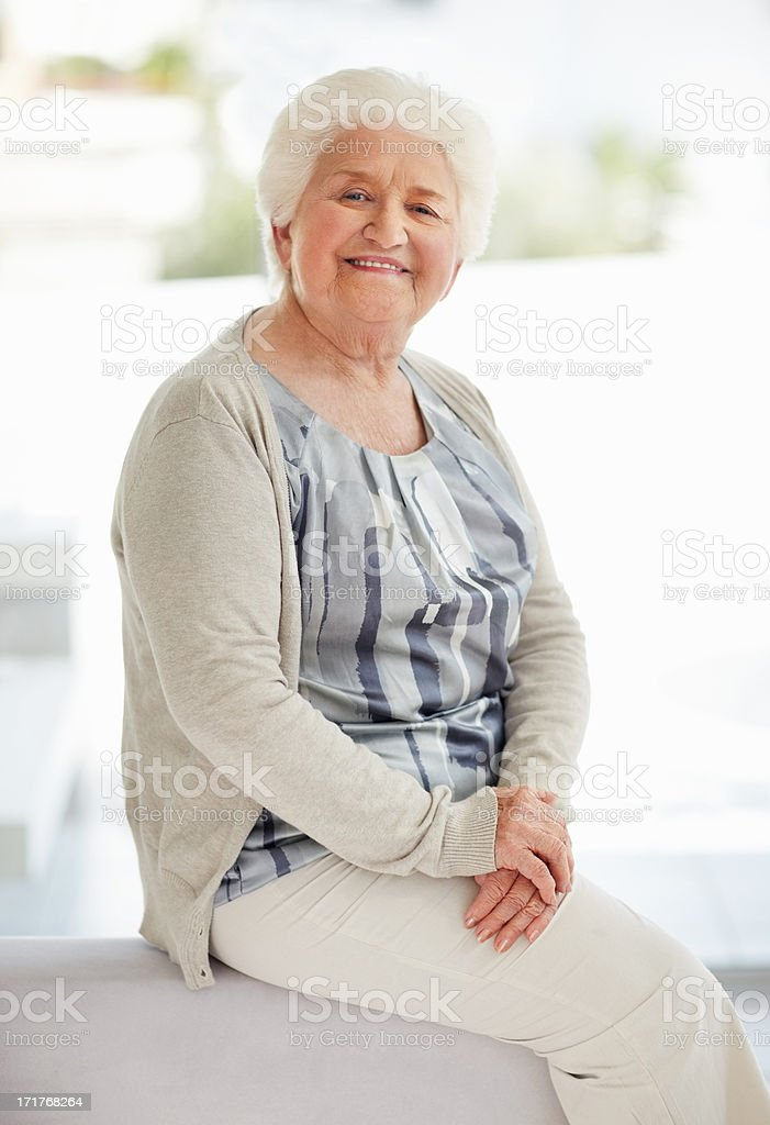 Happy senior woman relaxing on sofa at home stock photo
