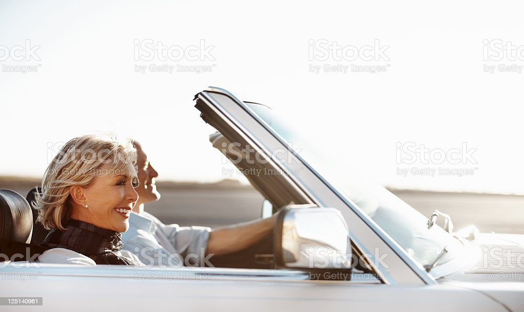 Happy senior woman riding in a car with her husband royalty-free stock photo