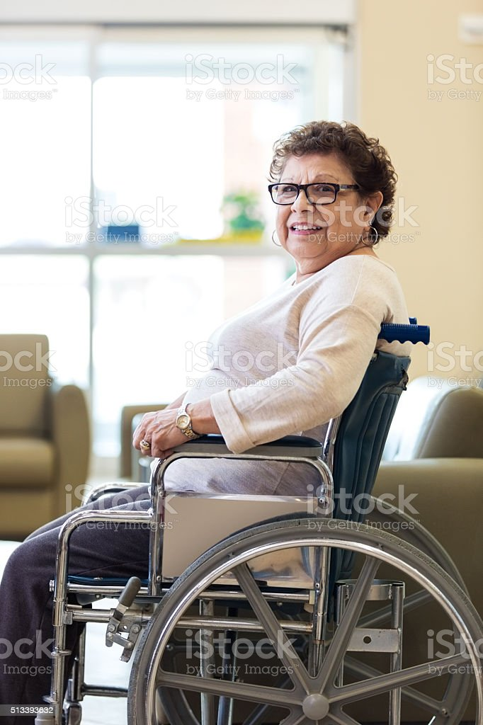 Happy senior woman sitting in wheelchair stock photo