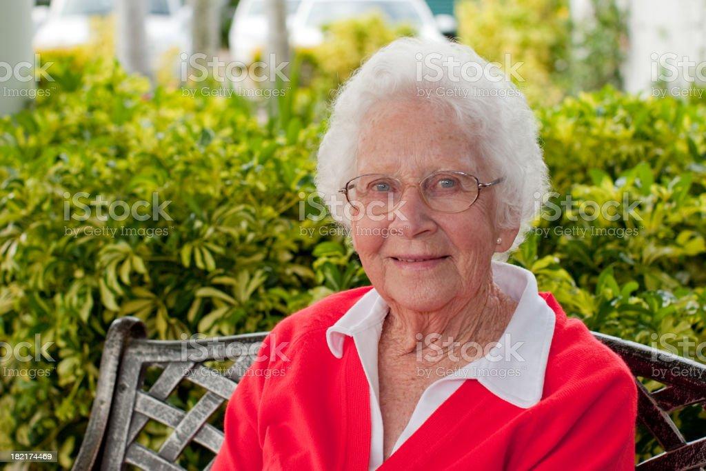 Happy Senior Woman sitting outdoors in the garden stock photo