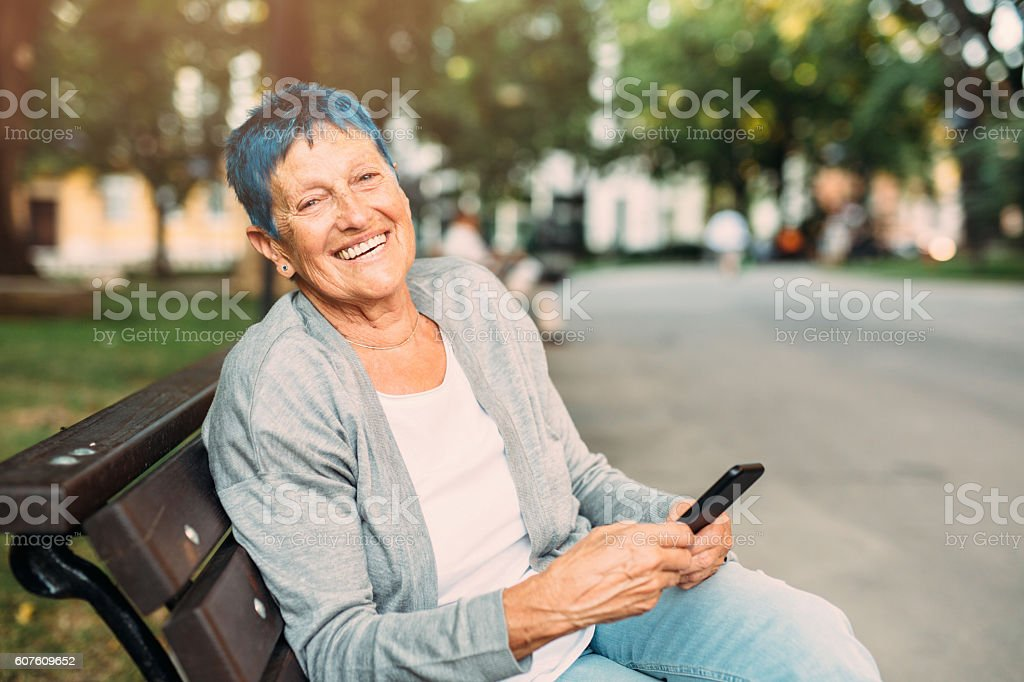 Happy senior woman texting stock photo