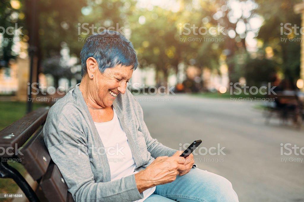 Happy senior woman texting stock photo