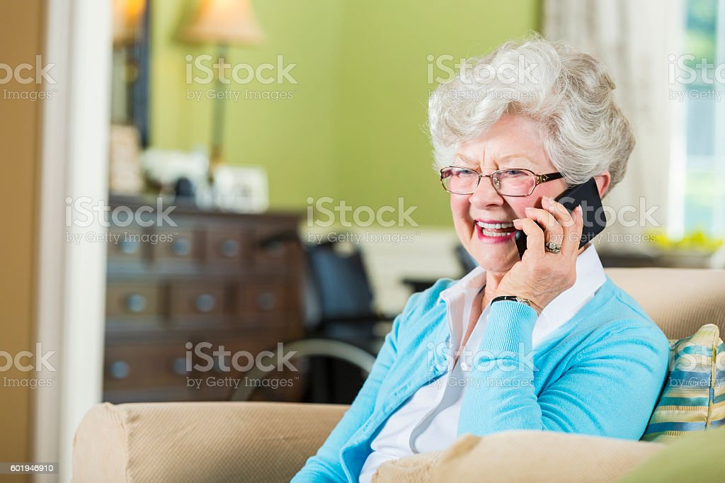 Happy senior woman uses smart phone to talk with family stock photo