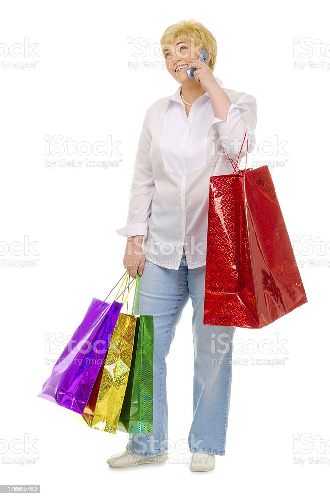 Happy senior woman with bags and mobile phone royalty-free stock photo