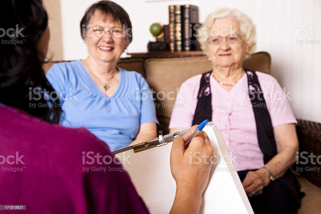 Happy senior woman with daughter. Doctor in foreground royalty-free stock photo