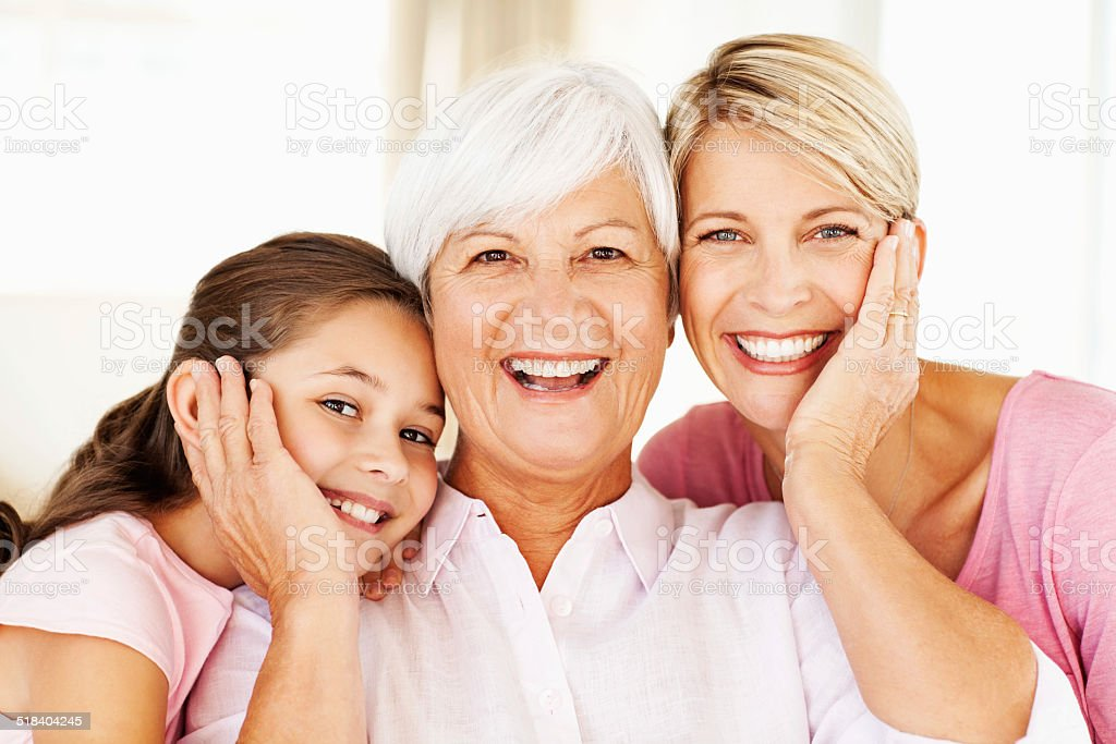 Happy Senior Woman With Grandchild And Daughter At Home stock photo