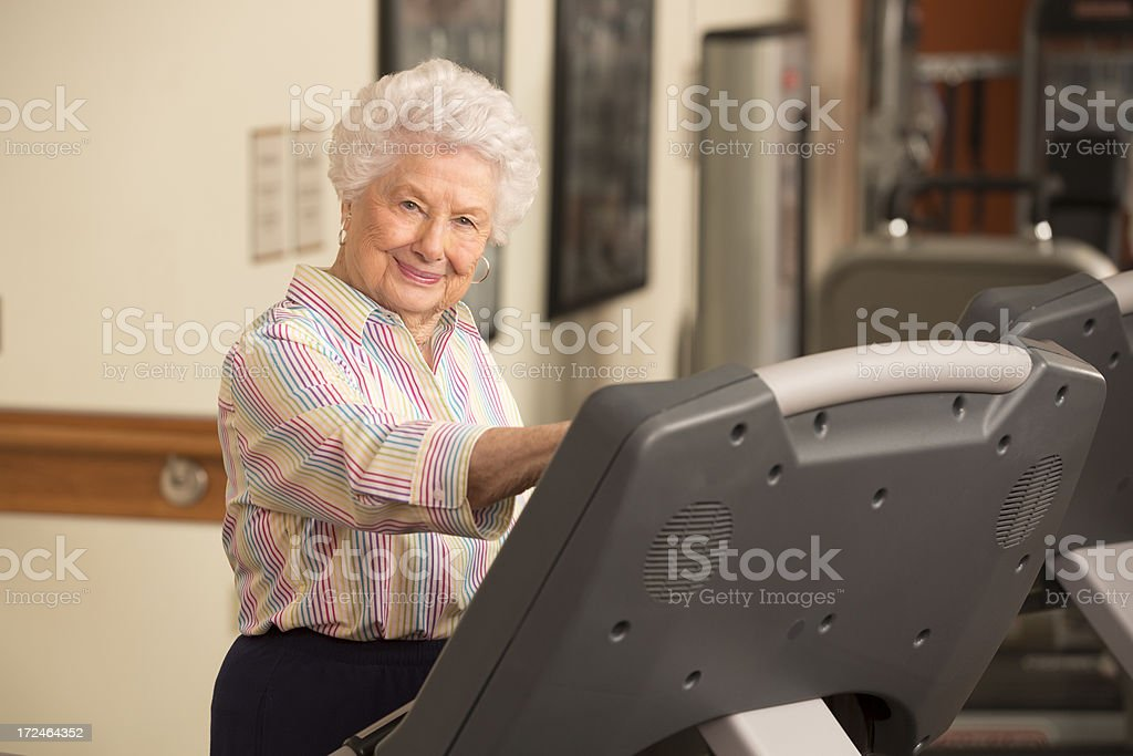 Happy senior woman working out on treadmill in gym royalty-free stock photo