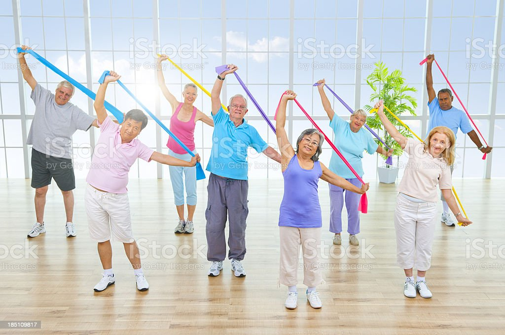 Happy seniors exercising with colorful bands in sunny room royalty-free stock photo