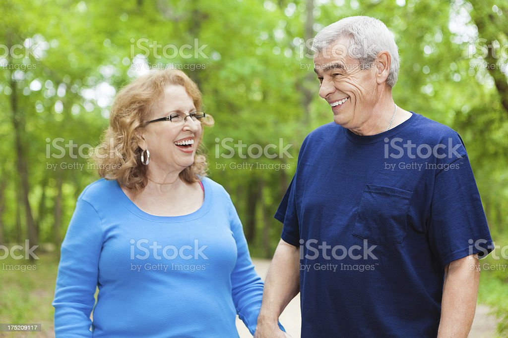 Happy seniors laughing and walking together at outdoor park royalty-free stock photo