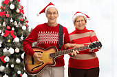 Happy seniors playing a guitar in front of Christmas tree
