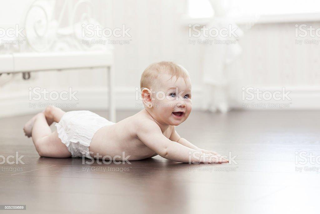 Happy seven month old baby girl crawling on hardwood floor stock photo