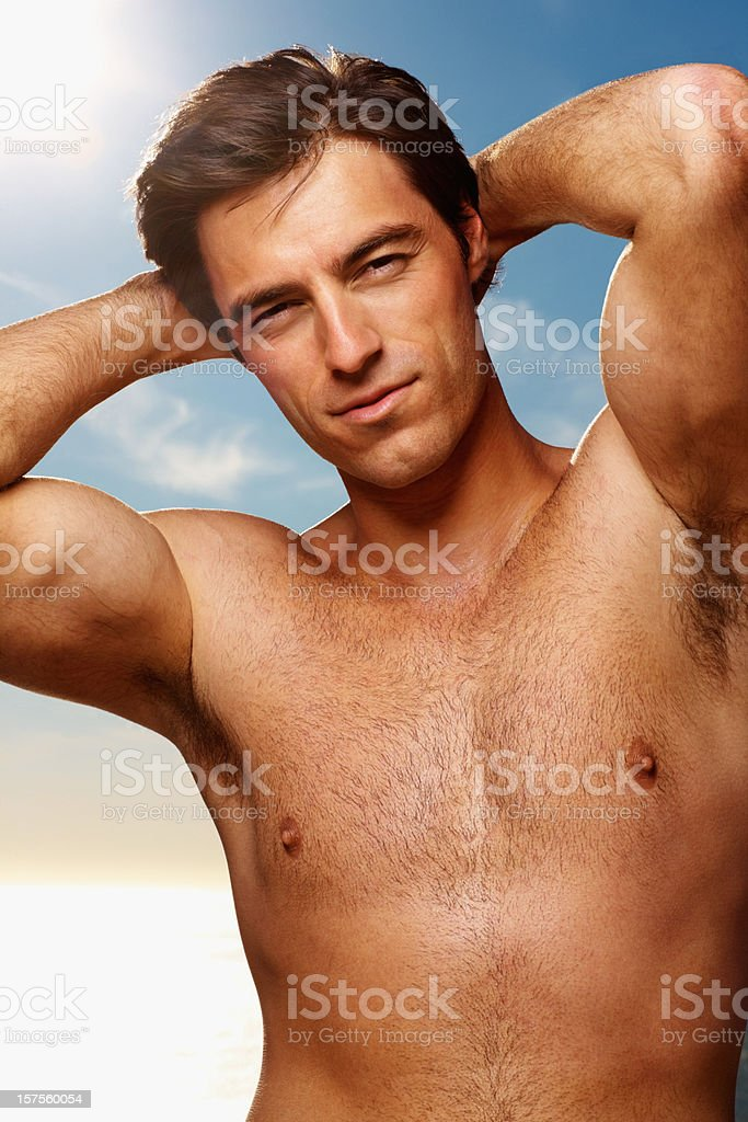 Happy sexy young guy posing by the sea royalty-free stock photo