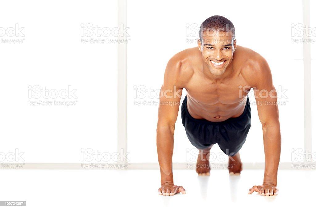 Happy shirtless guy doing push ups isolated on white royalty-free stock photo
