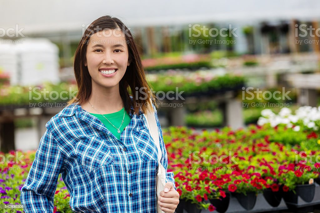 Happy shopper at a garden center full of flowers stock photo