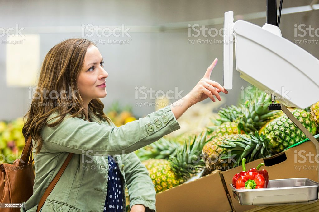 Happy shopper weighing produce stock photo
