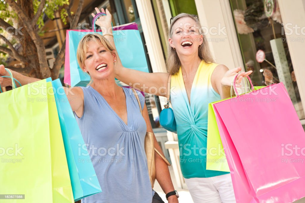 Happy Shoppers Outside Stores Holding Up Shopping Bags royalty-free stock photo