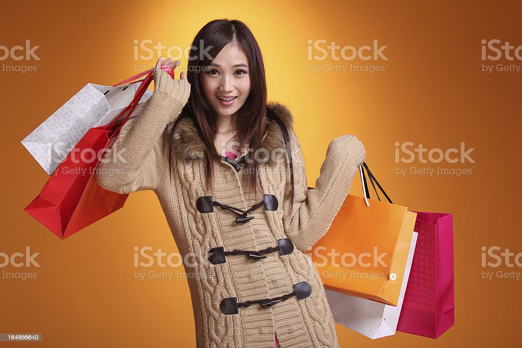Happy shopping asian woman, yellow background royalty-free stock photo