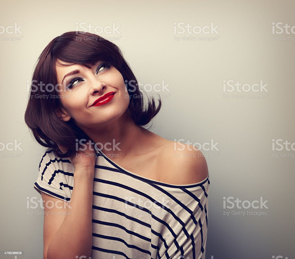 Happy short hair makeup woman thinking and looking up. Vintage stock photo