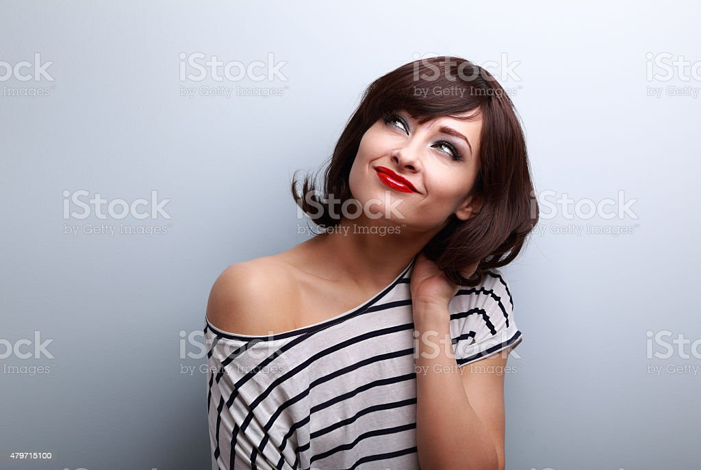 Happy short hair woman thinking and looking up stock photo