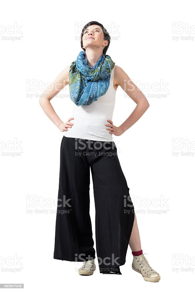 Happy short hair woman with hands on hips looking up stock photo