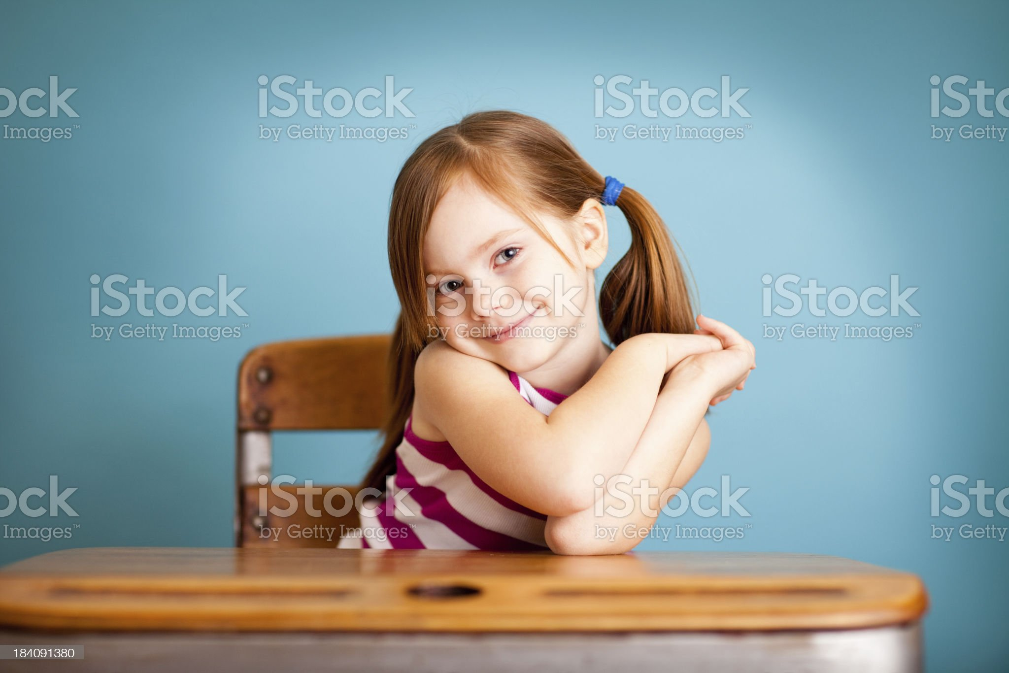 Happy, Shy Young Student Girl Sitting at School Desk royalty-free stock photo