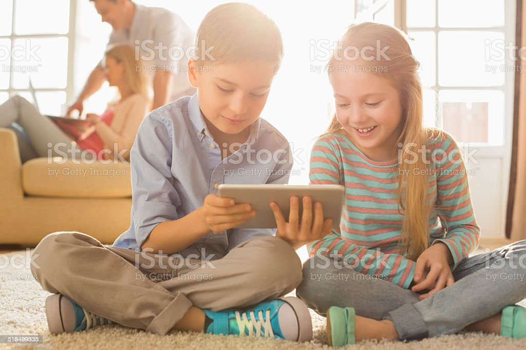 Happy siblings using digital tablet on floor stock photo