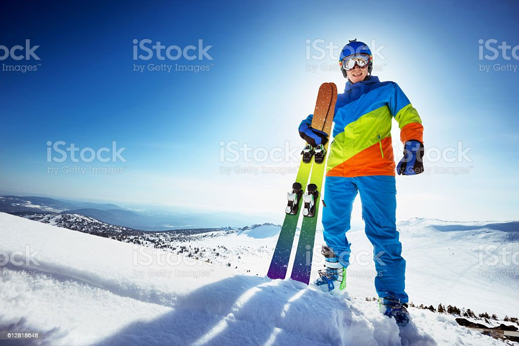 Happy skier in colorful clothes with ski stock photo