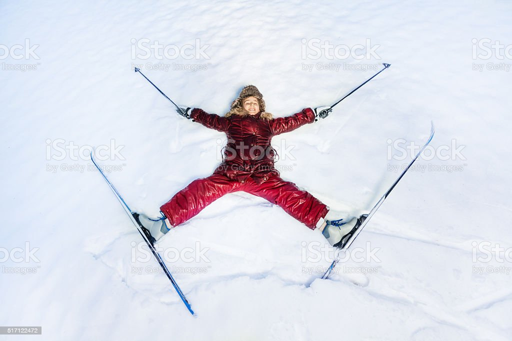Happy skier laying as a star on the snow stock photo