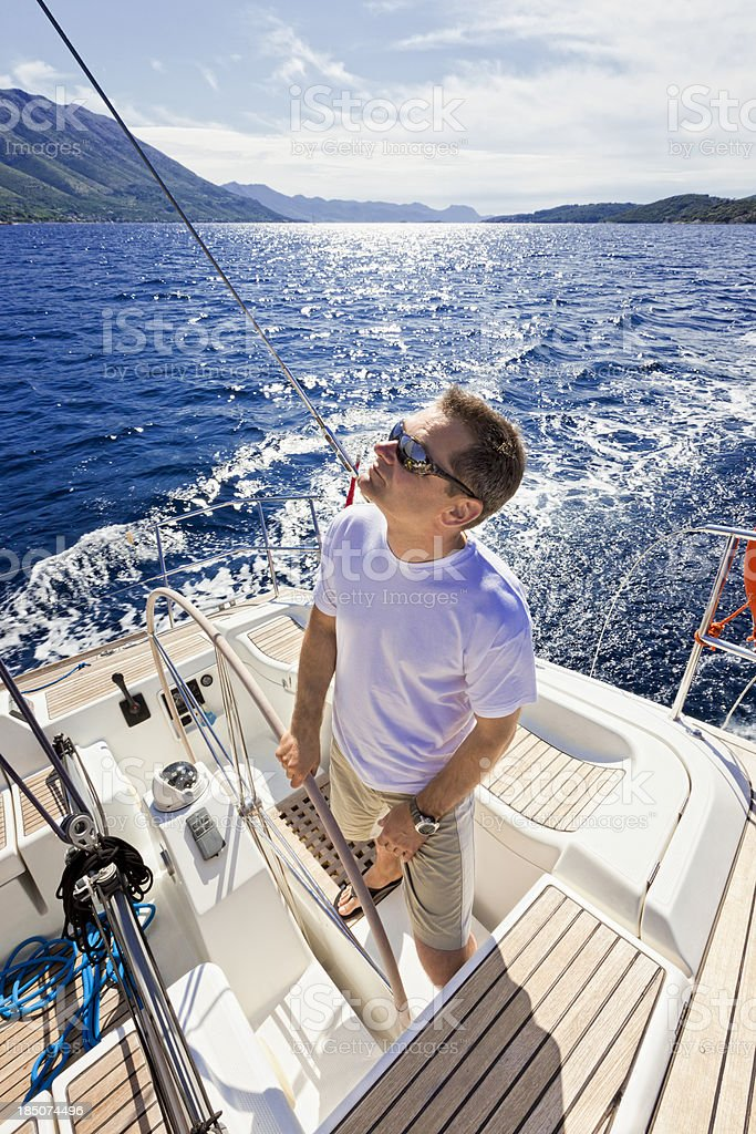 Happy skipper driving sailboat royalty-free stock photo
