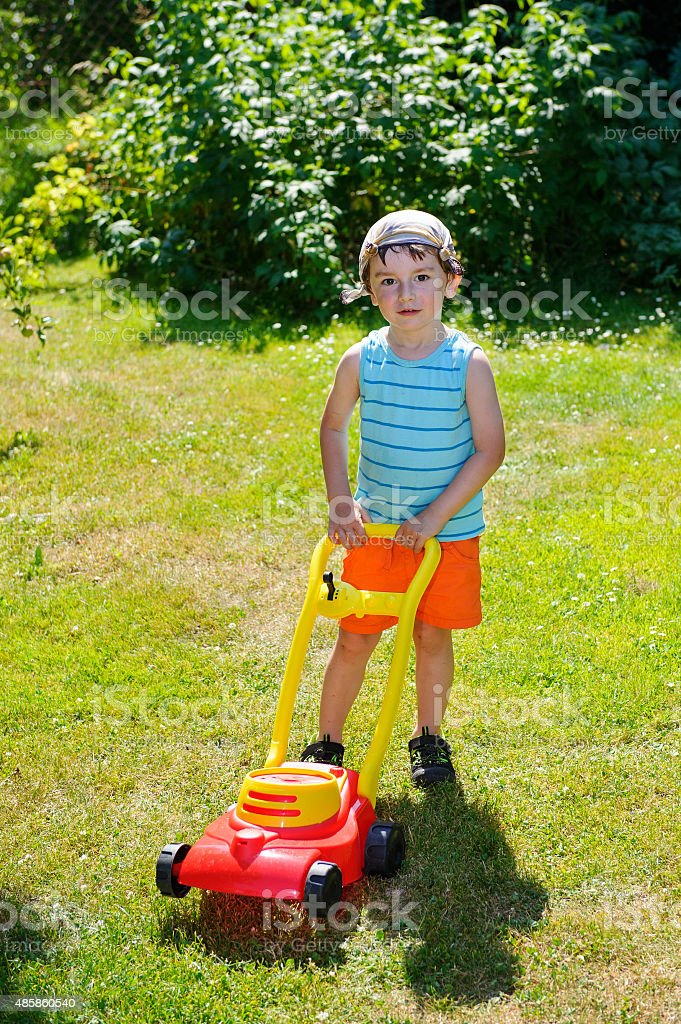 Happy small boy help with gardening with his lawn mower stock photo