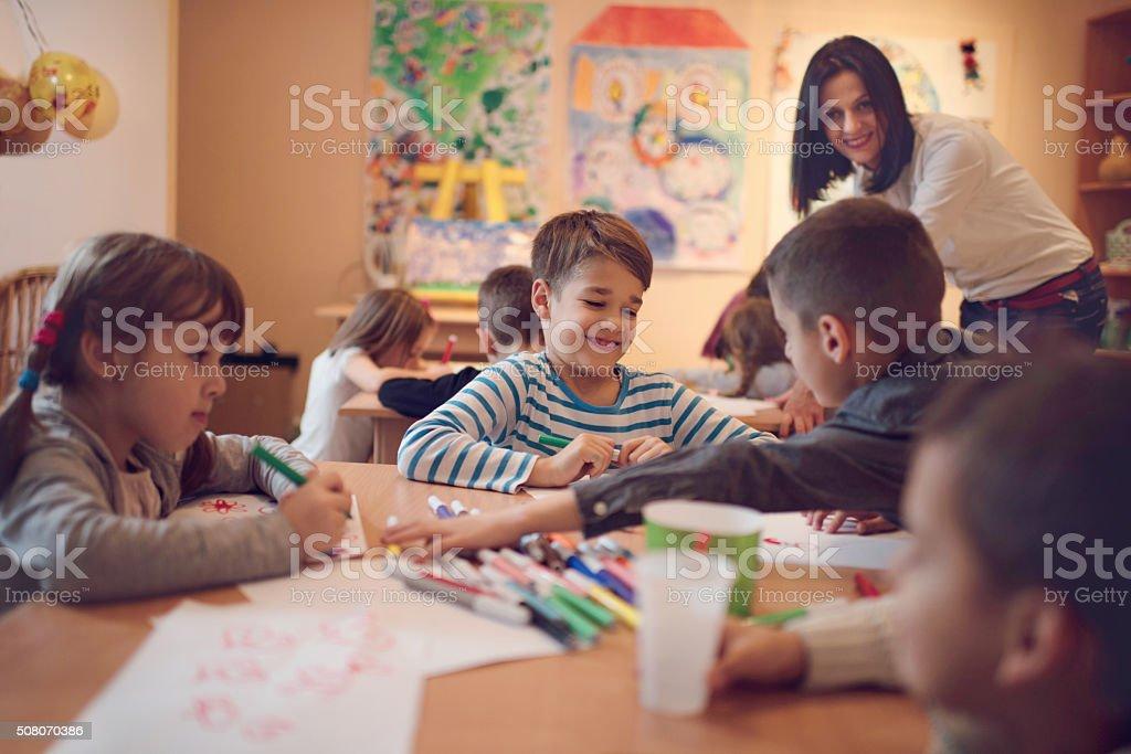 Happy small kid enjoying on a class in a preschool. stock photo