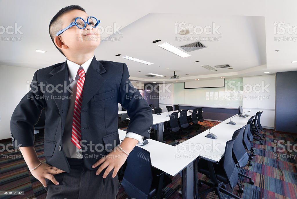 Happy smile little business boy in conference hall background stock photo