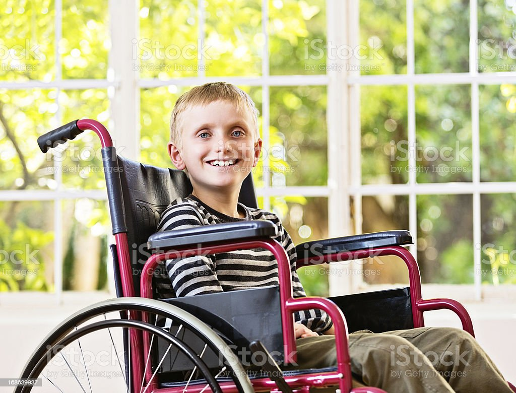 Happy, smiling 9-year-old boy sitting in wheelchair by window stock photo