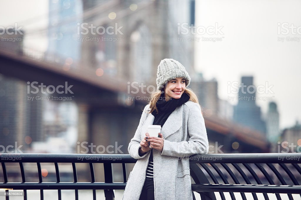 Happy smiling adult tourist woman holding paper coffee cup stock photo