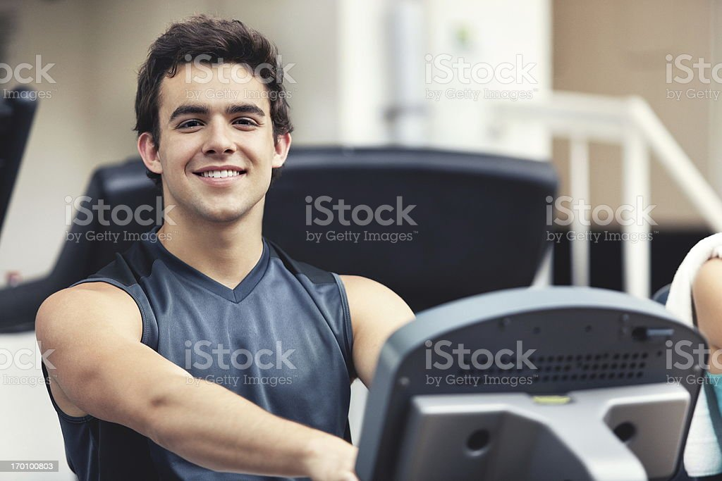 Happy smiling and beautiful man on a bicycle in gym. royalty-free stock photo