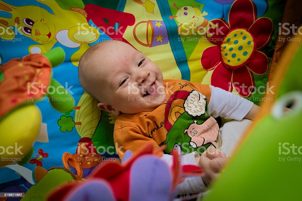 Happy smiling baby boy playing in colorful playpen stock photo