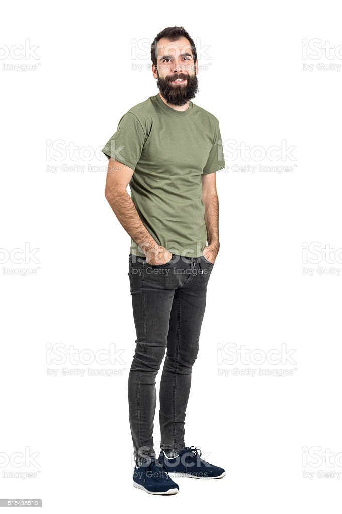 Happy smiling bearded hipster with hands in pockets stock photo