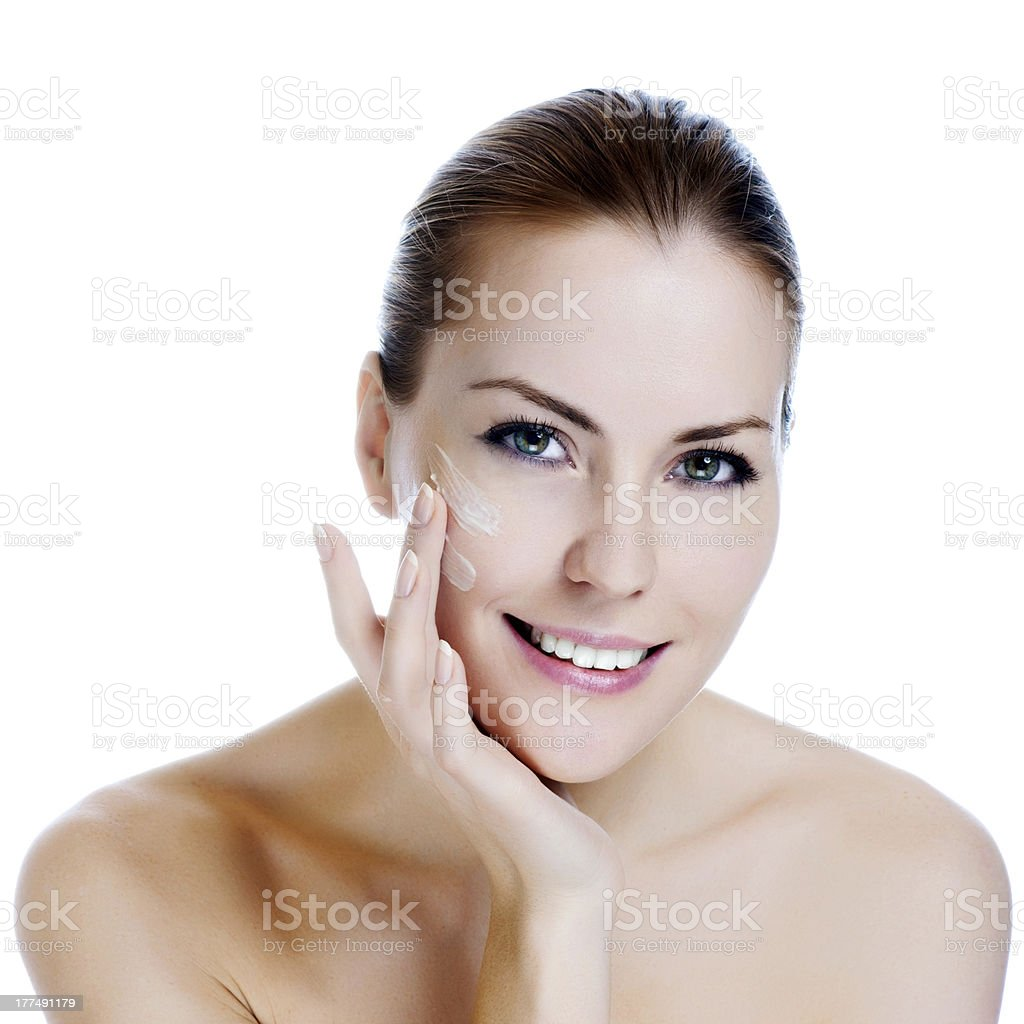 Happy smiling beautiful woman applying moisturizer cream on the face stock photo