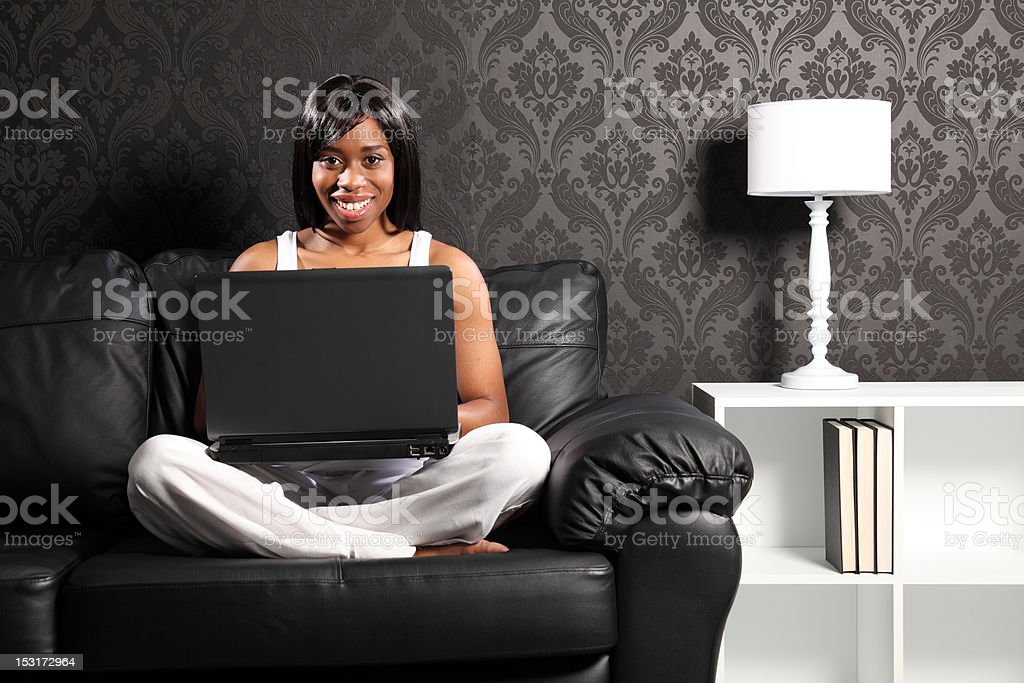 Happy smiling black woman on sofa surfing internet royalty-free stock photo
