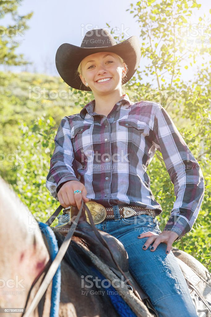 Happy Smiling Blonde Cowgirl sitting on her Horse stock photo